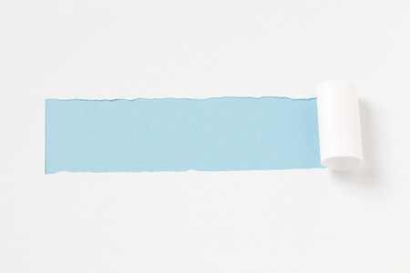 torn: torn paper on blue background Stock Photo