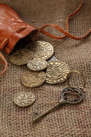 monete antiche: Dobloni d'oro con custodia in pelle e vecchia chiave su tela di sacco