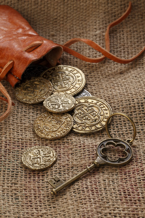 pouch: Gold Doubloons with leather pouch and old key on sackcloth Stock Photo