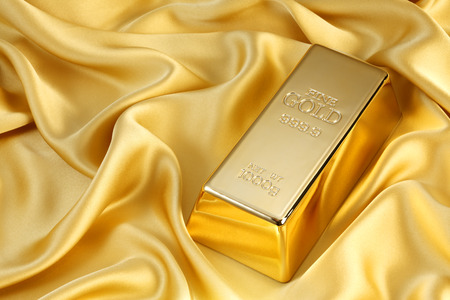 Photo of a 1kg gold bar on gold satin 스톡 콘텐츠