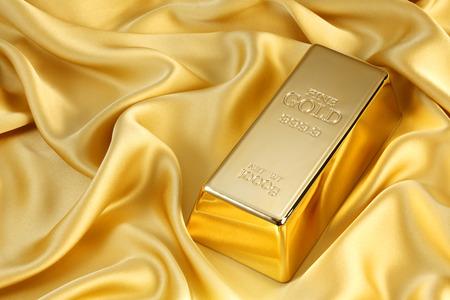 Foto van een 1kg gouden staaf op goud satijn Stockfoto