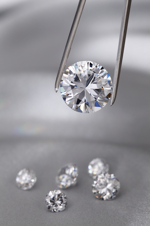 held: A round brilliant cut diamond held in tweezers Stock Photo