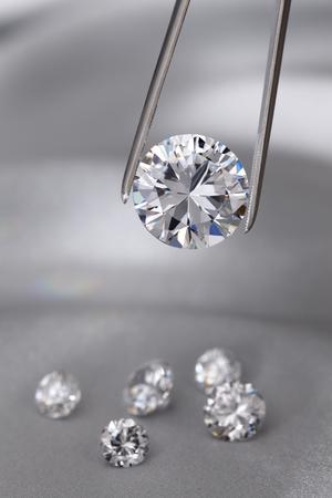 A round brilliant cut diamond held in tweezers Stockfoto