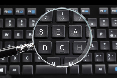 Search written on keyboard with magnifying glass
