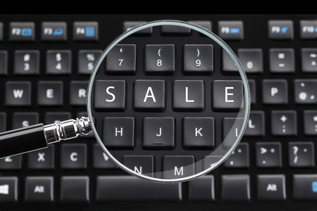 desktop computers: SALE written on keyboard with magnifying glass