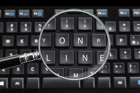 desktop computers: ON LINE written on keyboard with magnifying glass
