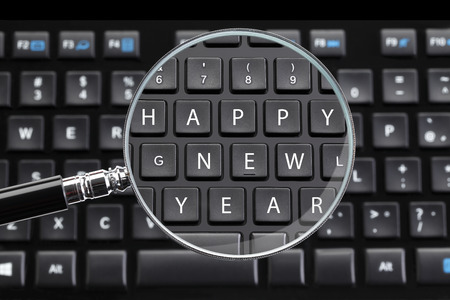 desktop computers: HAPPY NEW YEAR written on keyboard with magnifying glass