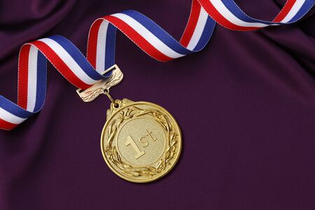 satin background: Gold medal on a Purple satin background Stock Photo