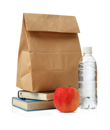 apple paper bag: Lunch time. Closeup of Brown paper lunch bag, red apple and bottle of water and book the isolated on white... Stock Photo