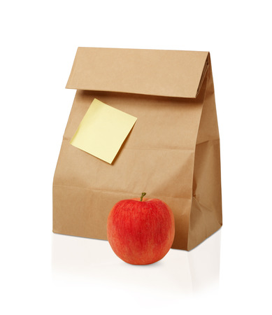 apple paper bag: Lunch time. Closeup of Brown paper lunch bag, red apple isolated on white...
