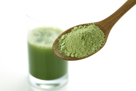 Close-up of the green vegetable juice in the glass and Powder of vegetables on spoon