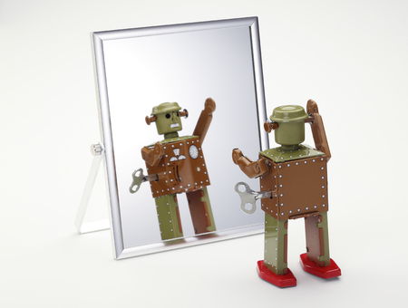 reflection in mirror: toy robot looking in the mirror