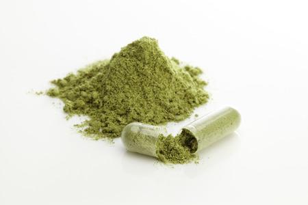 green powder: Herbal capsules and powder on white Stock Photo