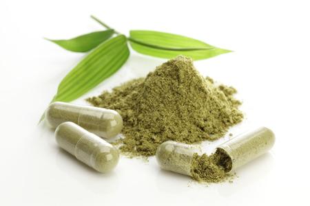 Herbal capsules and powder on white Stock Photo
