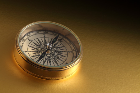 old compass on gold background Stock Photo