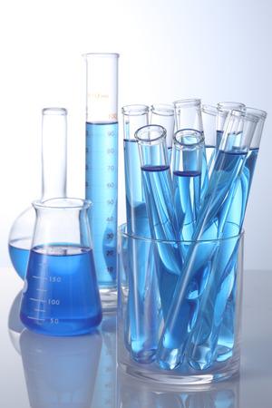白い背景上の青いサンプルと実験用ガラス器具