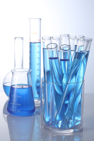 Laboratory glassware with blue samples on white background Imagens - 86033036