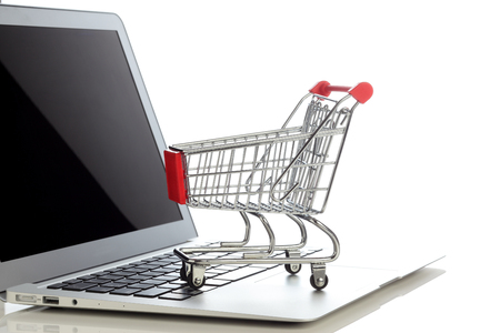 E-commerce. Shopping cart on laptop. Conceptual image.