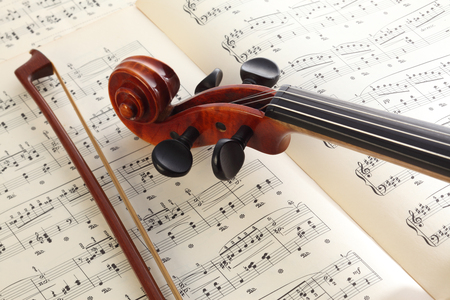 Close-up photo of vintage violin with bow and musical notes.