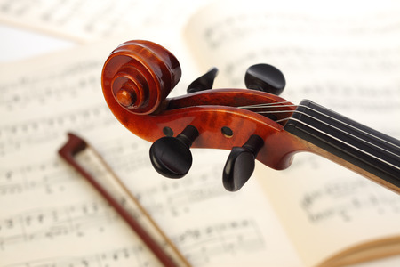 Close-up photo of vintage violin wit musical notes.