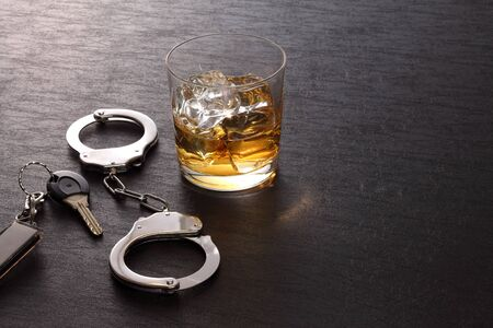 The concept for drink driving. Glass of alcohol, handcuffs, car keys