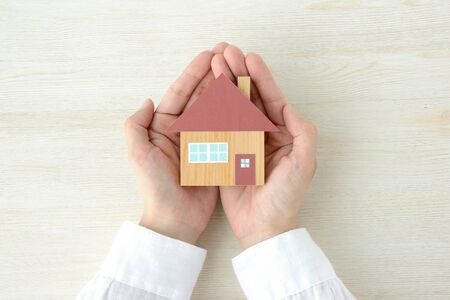 A house model wrapped in a hand