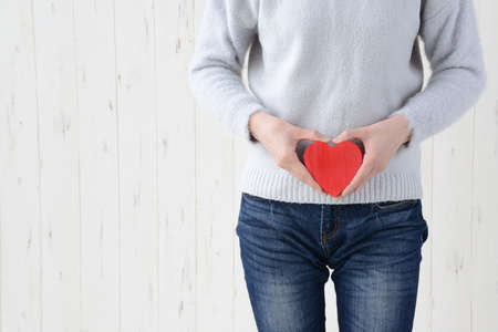 a woman with a heart near her stomach Stock Photo