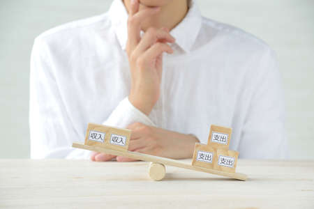 Women thinking about balance of income and expenditure 写真素材