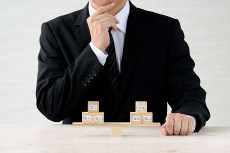 Businessmen considering balance of income and expenditure 写真素材