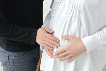 Maternity image of a couple attaching a hand to a pregnant woman's stomach