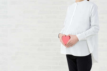 Maternity image of a pregnant woman with a heart object on her stomach
