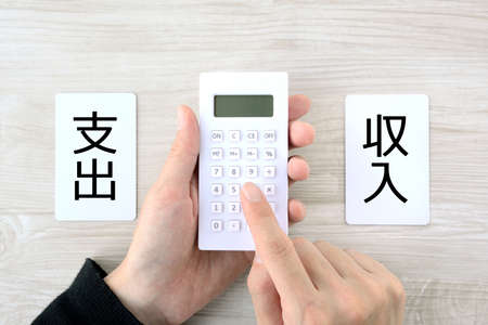 the hand of a person who calculates income and expenses
