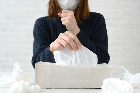 Woman taking tissue to bite runny nose 免版税图像