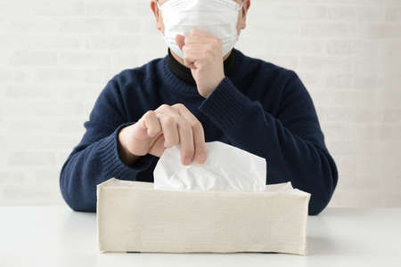 a man who takes a tissue to bite a runny nose