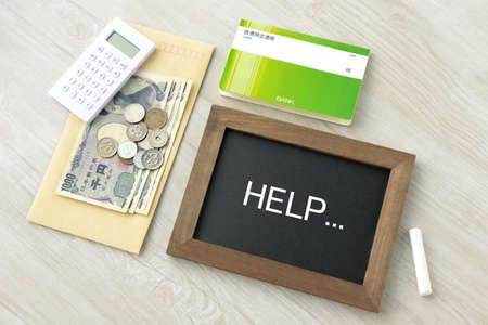 Blackboard with money and HELP letters Foto de archivo