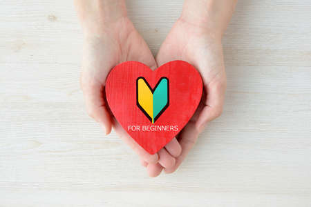 Woman's hand with heart object with beginner mark