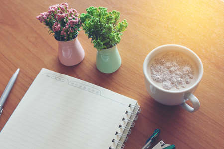 A hot cup of coffee to handle a notebook, a pen, a calculator, Staples and a vase on the table.