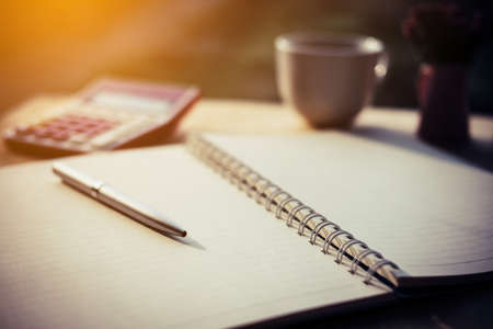 Pen, opened notebook, and coffee cup on working table in morning time on work day.