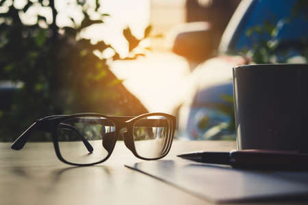 notebook, glasses, pen and cup of coffee on wooden background.