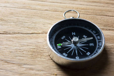 Close_up of magnetic compass on wooden table. Banco de Imagens
