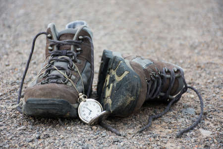 Old shoes and pocket watch on street, vintage style
