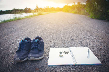 Old shoes pocket watch and notebook on the road, vintage style.