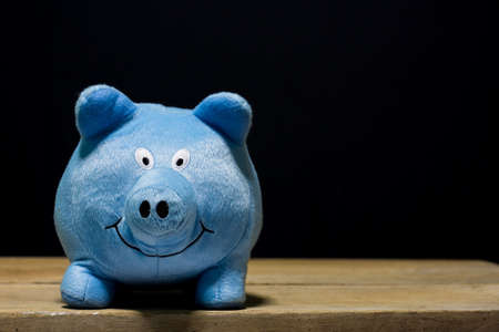 cute blue pig doll isolated on wooden table. Banco de Imagens
