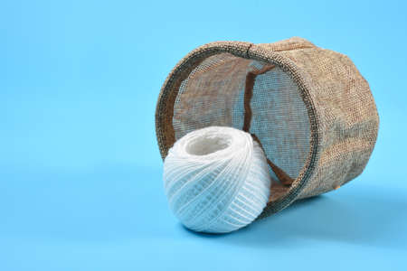A white thread rolls in front of a fallen sack. On a blue background. Banco de Imagens