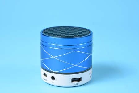 Horizontal blue wireless speaker on blue background. Banco de Imagens