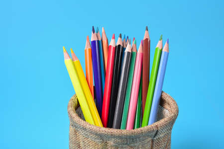Crayon in pencil box. Colorful wood pencils on blue background.