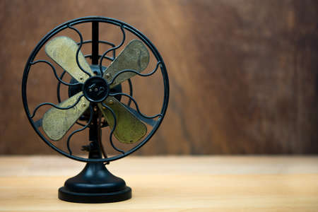 Retro electric fan on wood table with copy-space.