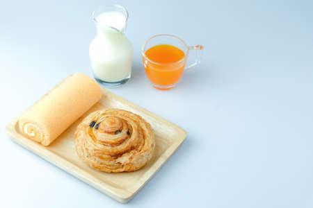 Breakfast including milk, danish pastry, orange juice and sweet rolls cake.