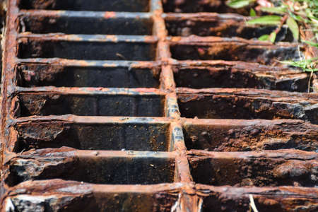 Top view of old and rusty metal covered on street drain hose. Rust metal texture background.