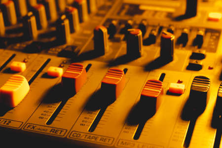 Professional audio mixing console in dim light.